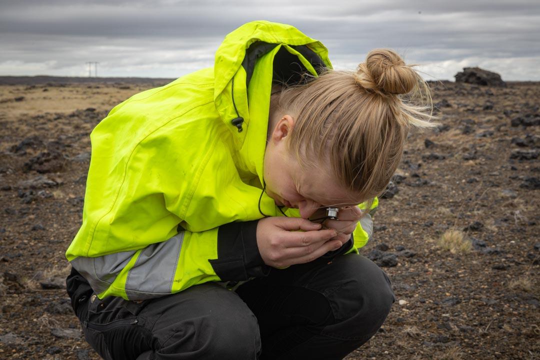 Ung kona skoðar gróður í stækkunargleri